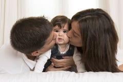 Madre y padre Kissing Daughter imagenes de archivo