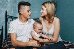 Madre y padre que abrazan a su hija del bebé imagen de archivo