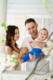 Madre y padre que abrazan a su hijo del bebé imagenes de archivo