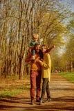 Madre y padre que llevan a cuestas al pequeño hijo que juega con el avión de papel con la inspiración La familia es fuente de ins fotografía de archivo libre de regalías