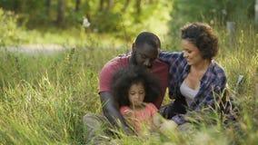 Madre y padre que muestran el afecto a la hija querida, riendo junto almacen de video