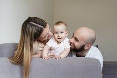 Madre y padre sonrientes que detienen a su hija del bebé que se sienta en cama en casa Concepto de familia feliz, hombre barbudo  foto de archivo