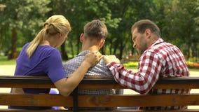 Madre y papá que cuidan que apoyan al hijo adolescente triste que se sienta en banco en el parque, crisis almacen de video