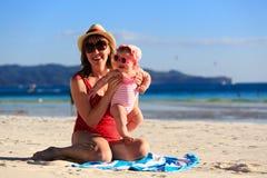 Madre y pequeña hija en la playa de la arena Foto de archivo libre de regalías