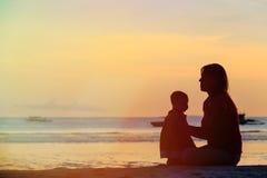 Madre y pequeña hija en la playa de la puesta del sol Imagen de archivo libre de regalías
