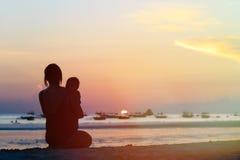 Madre y pequeña hija en puesta del sol Fotografía de archivo libre de regalías