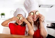 Madre y pequeña hija en sombrero del cocinero y delantal que juega con las rebanadas del pepino en ojos en cocina Imagenes de archivo