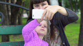 Madre y pequeña hija linda que toman el selfie con smartphone en el parque almacen de metraje de vídeo