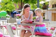 Madre y pequeña hija que beben en café imágenes de archivo libres de regalías