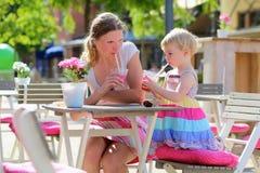 Madre y pequeña hija que beben en café imagen de archivo