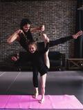 Madre y pequeña hija que hacen la pierna partida permanente que estira el ejercicio que mantiene el equilibrio imágenes de archivo libres de regalías