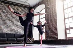 Madre y pequeña hija que hacen la pierna partida permanente que estira el ejercicio que mantiene el equilibrio imagen de archivo libre de regalías