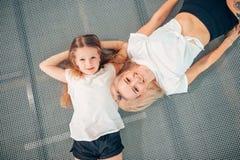 Madre y pequeña hija que juegan en el patio y que mienten en el trampolín fotos de archivo