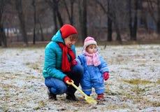 Madre y pequeña hija que juegan en invierno Imagen de archivo