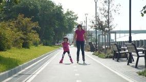 Madre y pequeña hija que patinan junto metrajes