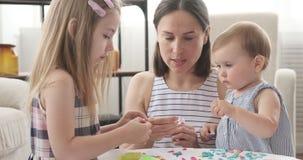 Madre y pequeñas hijas que juegan con plasticine almacen de video