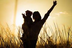 Madre y pequeñas siluetas de la hija en la puesta del sol Foto de archivo
