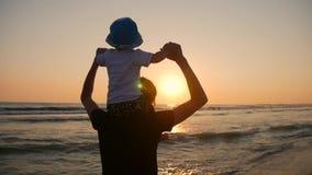 Madre y pequeño hijo que caminan y que juegan en la playa en la puesta del sol almacen de video