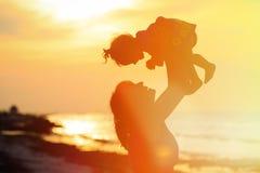 Madre y pequeño juego de la hija en la puesta del sol Imagen de archivo