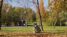 Madre y pequeños charla y beso del hijo en parque del otoño metrajes
