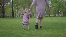 Madre y peque?a hija que corren alrededor con las manos de la tenencia en parque verde asombroso Mujer y ni?o que juegan en el pa almacen de metraje de vídeo