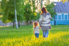 Madre y pequeña hija que caminan en parque soleado Fotos de archivo