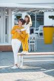 Madre y poca hija que se divierten en un parque en un día soleado agradable ropa casual que lleva amarilla y color blanco fotografía de archivo