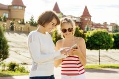 Madre y retrato adolescente de la hija La ciudad, la mamá y la hija del verano del fondo están mirando en smartphone Imagen de archivo libre de regalías
