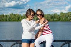 Madre y retrato adolescente de la hija la mamá y la hija están mirando en smartphone Foto de archivo