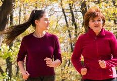 Madre y ropa de deportes que lleva y funcionamiento de la hija en bosque en la montaña imagenes de archivo