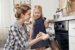 Madre y su comida que cuece de la hija en horno foto de archivo