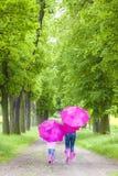 Madre y su hija con los paraguas Imagenes de archivo