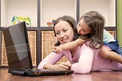 Madre y su hija delante de la computadora portátil Imágenes de archivo libres de regalías