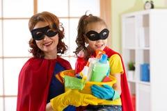 Madre y su hija en traje del super héroe Momia y niño listos para contener la limpieza Houseworking y economía doméstica Imagenes de archivo