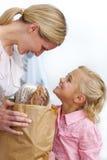 Madre y su hija que desempaquetan el bolso de tienda de comestibles foto de archivo libre de regalías