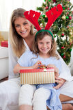 Madre y su hija que desempaquetan los regalos de la Navidad Foto de archivo libre de regalías
