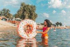 Madre y su hija que relajan y que se divierten en el agua en un buñuelo inflable fotos de archivo