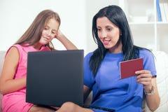 Madre y su hija que usa un cuaderno Foto de archivo