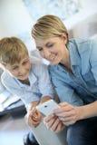 Madre y su hijo que juegan en smartphone Fotografía de archivo