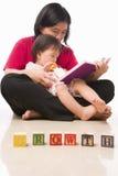 Madre y su libro de lectura de la niña Foto de archivo