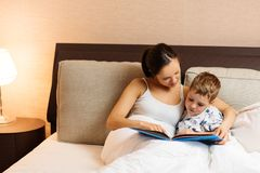 Madre y su libro de lectura del hijo Fotos de archivo libres de regalías