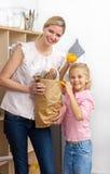 Madre y su niña que desempaquetan el bolso de tienda de comestibles Imágenes de archivo libres de regalías