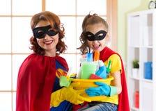 Madre y su niño en traje del super héroe Momia y niño listos para contener la limpieza Houseworking y economía doméstica Foto de archivo libre de regalías