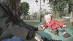 Madre y su pequeña hija adentro al aire libre La mamá lleva a cabo la mano del ` s del bebé almacen de metraje de vídeo