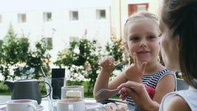Madre y su pequeña hija en café al aire libre metrajes