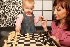 Madre y su pequeña hija que juegan a ajedrez Imagen de archivo libre de regalías