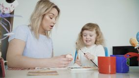 Madre y su pequeña hija que pintan los huevos de Pascua