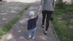 Madre y su poco hijo en el paseo que lleva a cabo las manos, el concepto de maternidad y la ni?ez almacen de metraje de vídeo