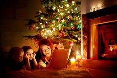 Madre y sus hijas que leen un libro Fotografía de archivo