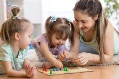 Madre y sus niños que juegan en juego de mesa imagen de archivo libre de regalías